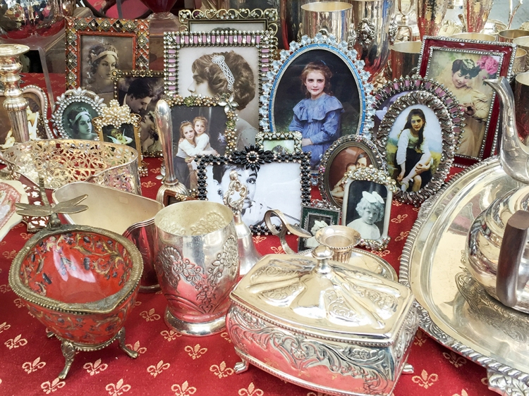 Delicate picture frames and antique tableware at a stand in Piazza Santo Spirito