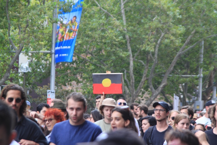 The Australian Aboriginal flag held high above the crowds stands a reminder that the strength of the first peoples of this continent will never be forgotten.